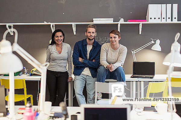 Portrait of confident multi-ethnic business colleagues sitting on desk against wall at creative office