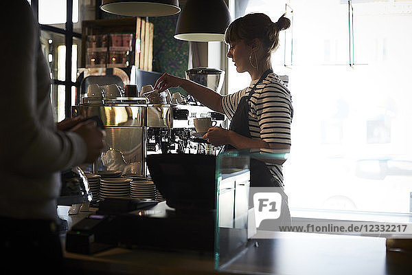 Female barista preparing coffee while customer standing at checkout counter