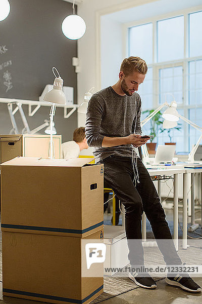 Full length of businessman using smart phone by cardboard boxes at office