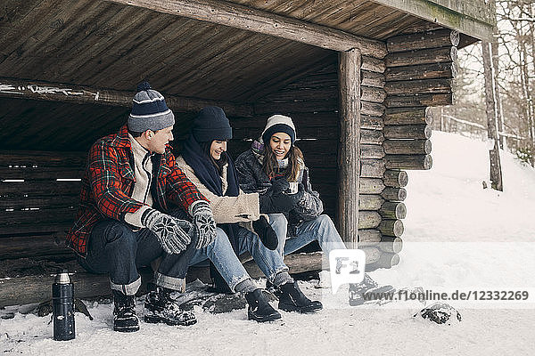 Friends sharing drink while sitting at log cabin during winter