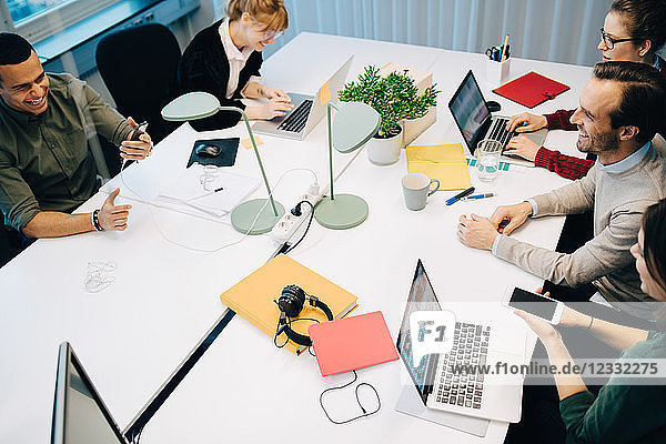 High angle view of happy multi-ethnic business coworkers sitting at desk while discussing in board room
