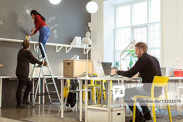 Young businessman using laptop while female colleagues rubbing wall at creative office