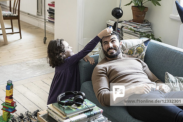 High angle view of girl keeping toy block on father's head lying on sofa at home