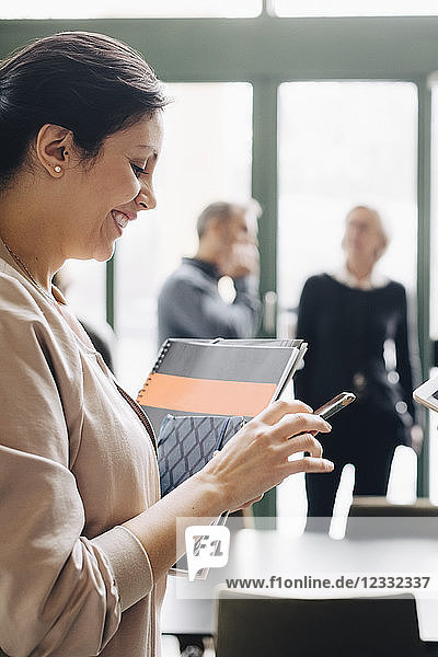 Smiling businesswoman using phone with coworkers in background