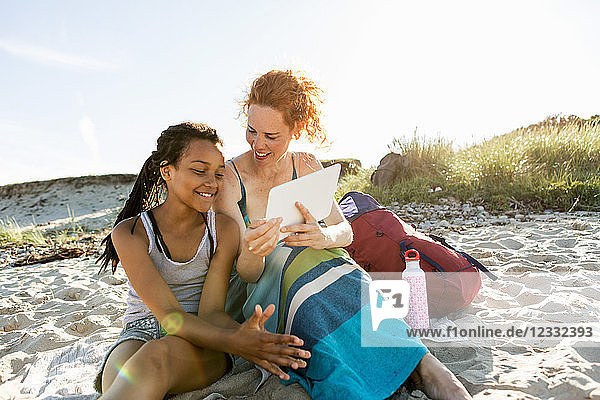 Smiling mother sharing digital tablet with daughter sitting on sand at beach against sky
