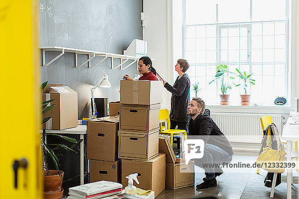 Multi-ethnic colleagues working by cardboard boxes stack at creative office