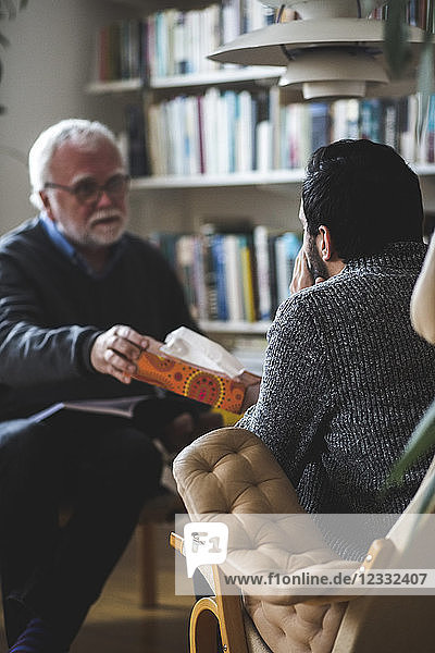 Therapist giving tissue box to male patient at home office