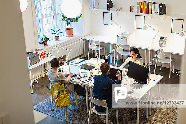 High angle view of multi-ethnic colleagues using technologies at desk in creative office