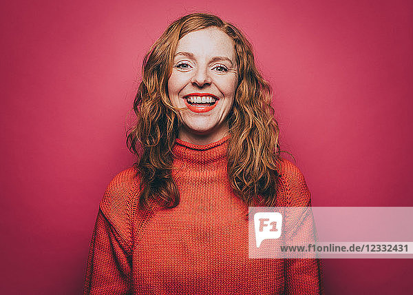 Portrait of smiling woman in orange top against pink background Portrait of smiling woman in orange top against pink background