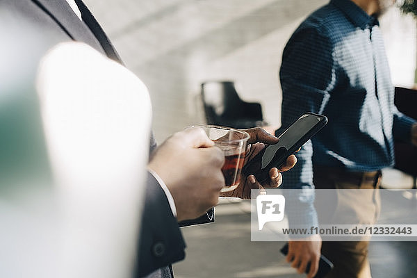 Midsection of businessman using mobile phone while having tea at office