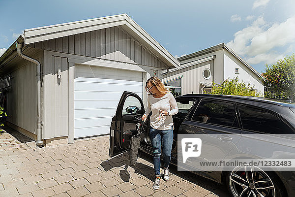 Full length of woman standing by car outside house on sunny day