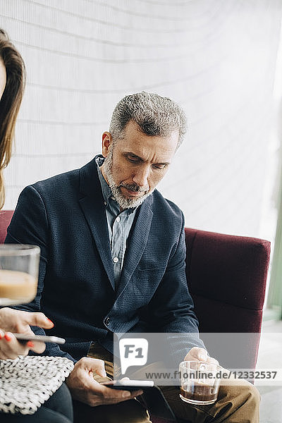 Business people using mobile phones and having drink while sitting on couch during conference