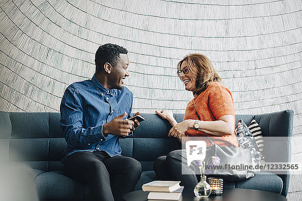 Happy male and female colleagues talking while sitting on couch against wall