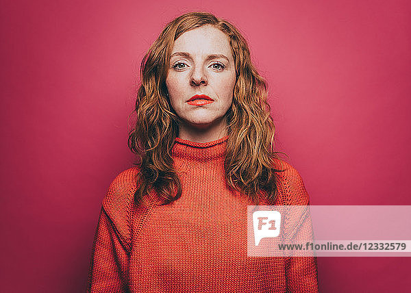 Portrait of confident woman in orange top over pink background