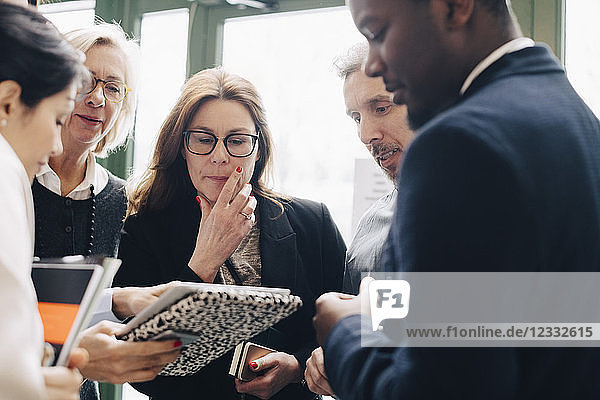Male and female colleagues looking at file in meeting