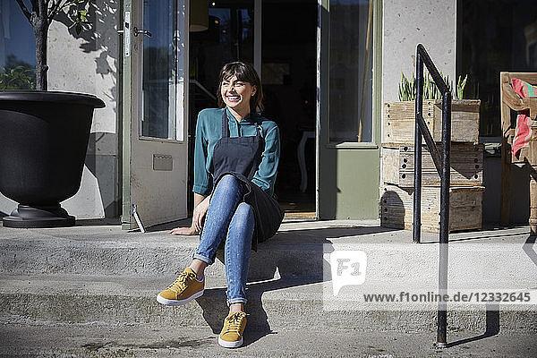 Full length of smiling female owner sitting on steps outside store