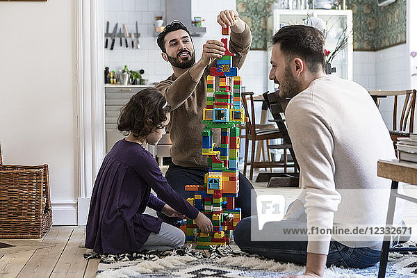 Happy gay men playing blocks with daughter at home