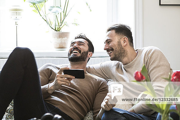 Cheerful gay couple with smart phone sitting on sofa against window at home