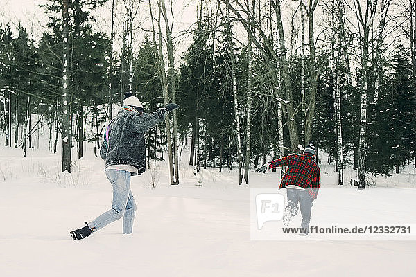 Playful friends running by trees on snow covered landscape