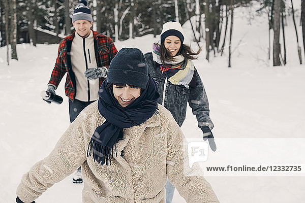 Cheerful friends walking on snow covered field