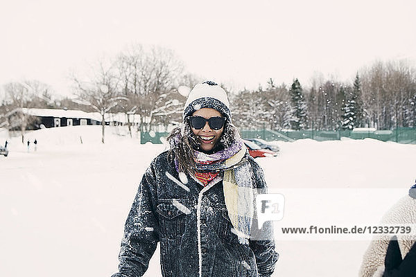 Portrait of mid adult woman standing on snow covered field