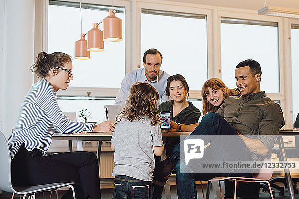 Smiling businessman showing smart phone to son while sitting by colleagues at creative office