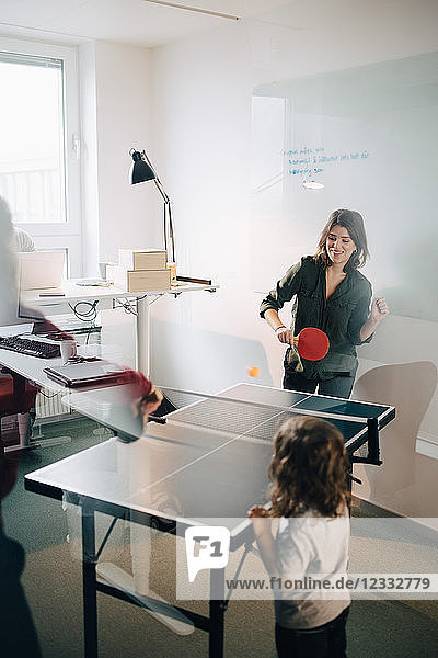 Boy looking at female professionals playing table tennis in creative office