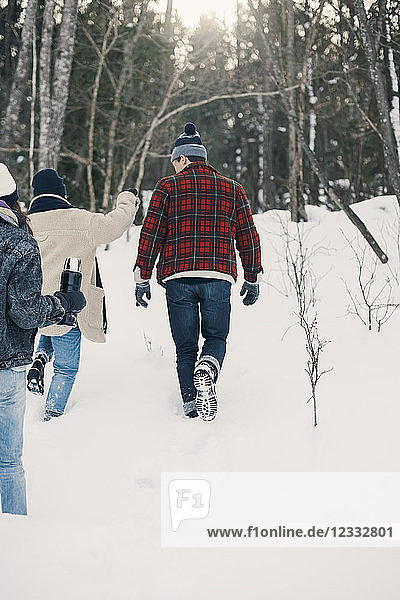 Rear view of friends walking on snow covered field