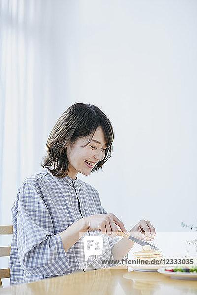 Young Japanese woman eating pancakes