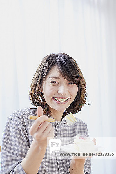 Young Japanese woman eating cake