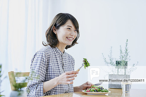 Young Japanese woman eating salad
