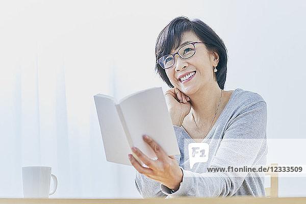 Japanese senior woman reading book at table
