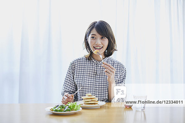 Young Japanese woman eating pancakes