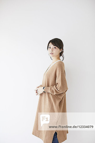 Young Japanese woman against white wall