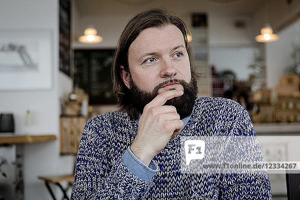 Man with beard sitting in cafe  portrait