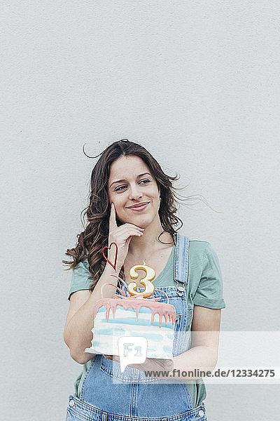 Portrait of smiling woman presenting Birthday cake