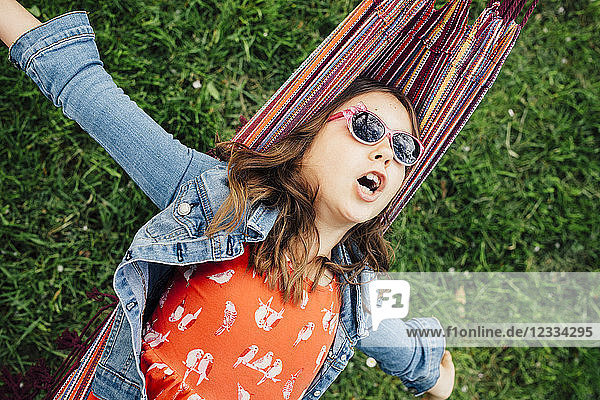 Portrait of singing girl wearing sunglasses lying in hammock