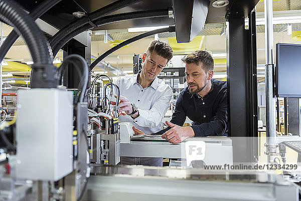 Two men examining machine in factory