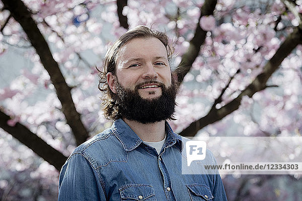 Portrait of bearded man in front of blossoming cherry tree