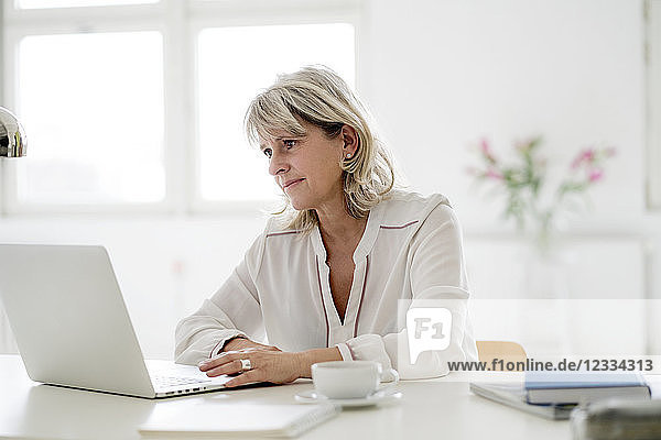 Smiling mature businesswoman working on laptop at desk
