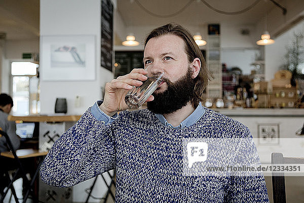 Man with beard sitting in cafe  drinking water