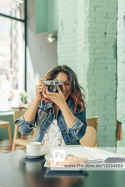 Laughing woman sitting at coffee shop taking pictures with camera