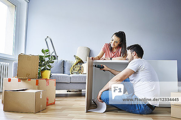 Couple in new apartment assembling furniture together