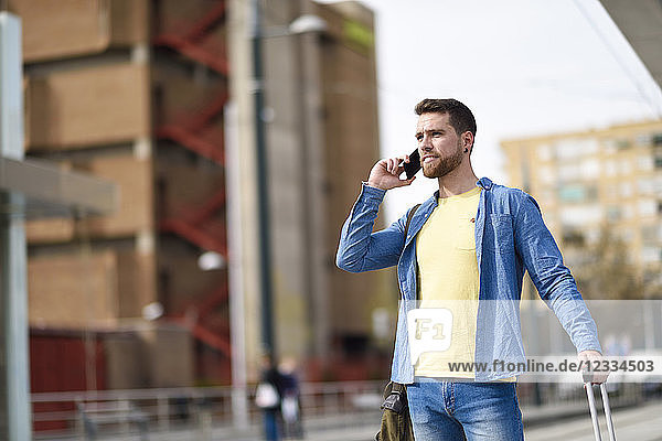 Young man with smartphone at station