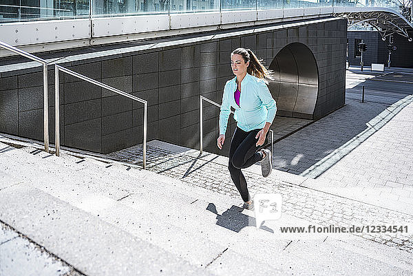 Young woman running on stairs in the city