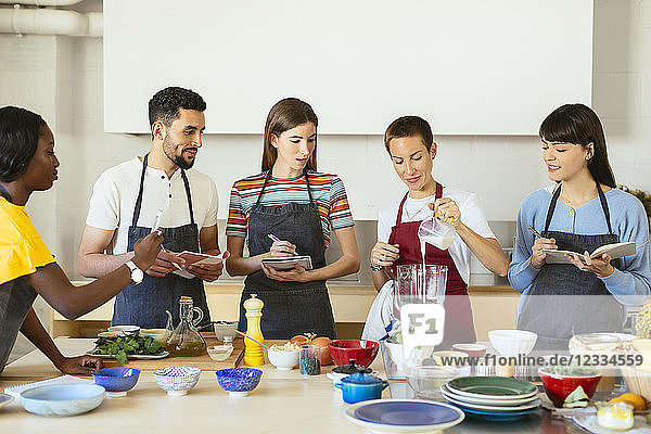 Friends and instructor in a cooking workshop preparing a smoothie