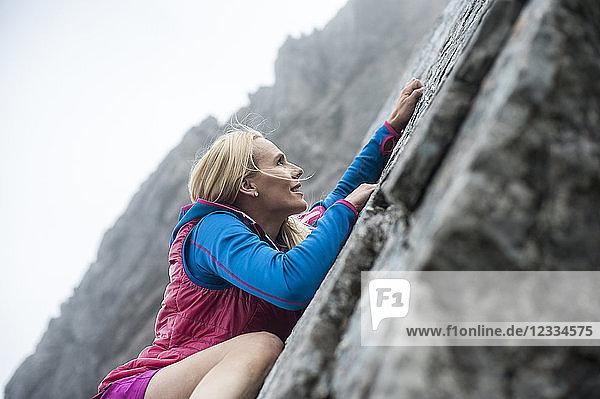 Austria  Salzburg State  Filzmoos  Female hiker climbing on rock