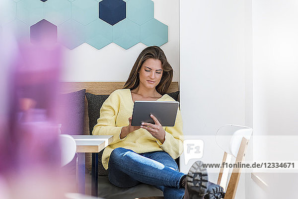 Relaxed young woman using tablet in a cafe