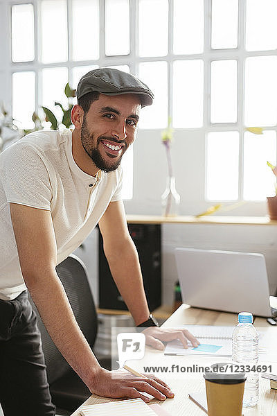 Portrait of smiling young man taking notes at desk in office