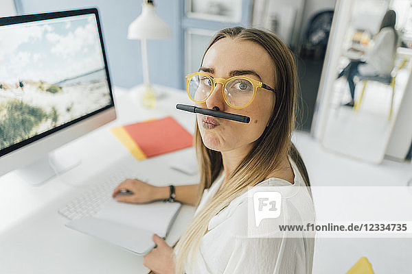 Portrait of funny young woman at desk pouting mouth